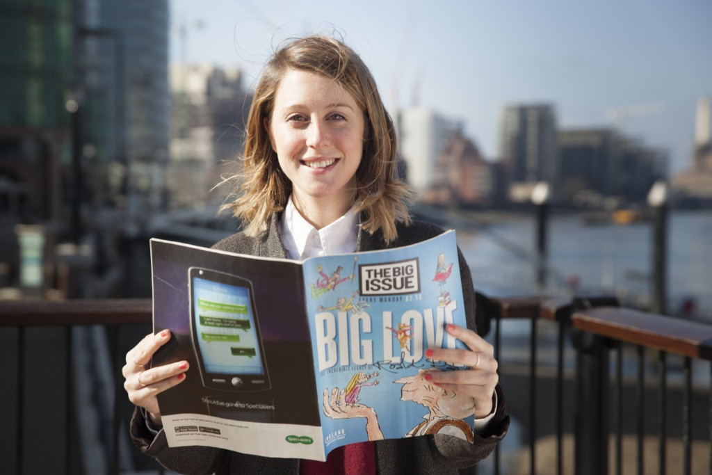 portrait photograph of female holding big issue magazine