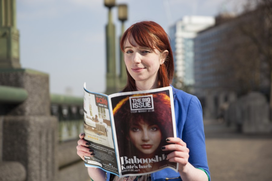 portrait of female holding big issue magazine